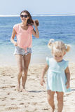 Beautiful young mother with her little daughter at the beach. Portrait of beautiful young mother wearing sunglasses  with her little daughter at the beach Stock Photos