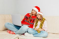 Beautiful young mother and her little daughter dressed in Santa stock images
