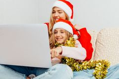 Beautiful young mother and her little daughter dressed in Santa stock image