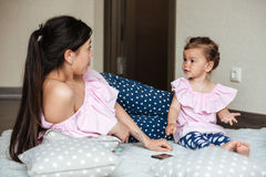 Beautiful young mother with her little daughter lies on bed Royalty Free Stock Photo