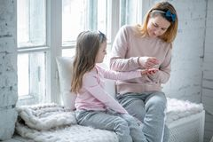 Beautiful young mother and her little daughter are sitting by the window together and painting their nails. Maternal care and love royalty free stock photo