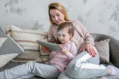 Beautiful young mother and her little daughter are watching movies together and playing on the tablet while sitting on the sofa. stock photo