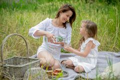 Beautiful young mother and her little daughter in white dress having fun in a picnic. They are sitting on a plaid and mom pours royalty free stock photos