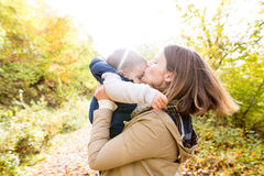 Beautiful young mother with her son in autumn forest. Stock Images