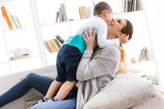 Beautiful young mother and her son having fun at home. Portrait of beautiful young mother and her son having fun at home royalty free stock images