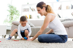 Beautiful young mother and her son having fun at home. Portrait of beautiful young mother and her son having fun at home stock photography