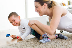 Beautiful young mother and her son having fun at home. Portrait of beautiful young mother and her son having fun at home stock images