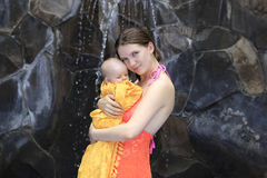 Beautiful young mother is holding baby girl outside near pool. Stock Photography