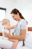 Beautiful young mother holding cute baby indoors Royalty Free Stock Image