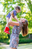 Beautiful young mother holding her happy little kid girl in arms Royalty Free Stock Image
