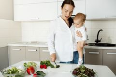 Beautiful young mother holding little son on hands in kitchen showing him how to cut vegetables for salad. Child looking. At mother hands with big interest Royalty Free Stock Images