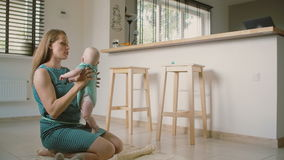 A beautiful young mother is holding up her adorable smiling baby helping him to stand up and talking to him. Slow motion stock footage