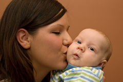 Beautiful Young Mother and Infant Boy. Young beautiful brunette mother holding her newborn baby boy Royalty Free Stock Photo