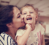 Beautiful young mother kissing her joying happy cute daughter Stock Photo