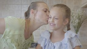 Beautiful young mother and little cute daughter cook in the kitchen together. Happy family. Mom kisses a girl soiled in. Beautiful young mother and little cute stock video