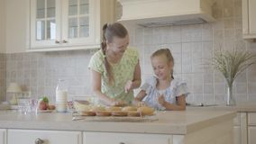 Pretty young mother and little cute daughter cook in the kitchen together. Real happy family. Relationship mom and. Beautiful young mother and little cute stock video footage