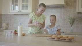 Beautiful young mother and little cute daughter cook in the kitchen together. Happy family. Relationship mom and. Beautiful young mother and little cute daughter stock video