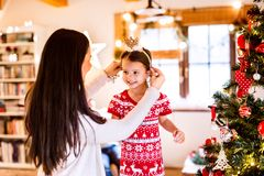 Young mother with daughter at Christmas tree at home. Royalty Free Stock Photography