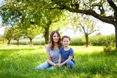 Beautiful young mother and little daughter sitting on green grass and resting stock photo