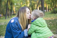 Beautiful young mother with long hair kisses her young son sitti. Ng on a rug in an autumn park on a blurred background of trees Stock Images