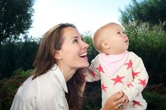Beautiful young mother looking away with cute baby outdoors Royalty Free Stock Images