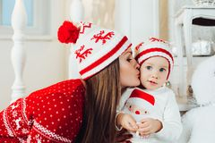 Mother looking at camera and while wearing hat to daughter