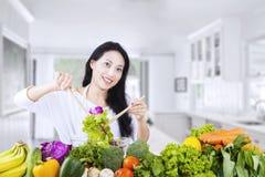 Beautiful woman makes salad at home Royalty Free Stock Photos