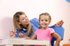 Beautiful young mother painting with daughter Stock Image