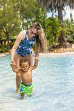 Beautiful young mother playing with her son on the pool royalty free stock images