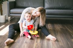 Beautiful young mother playing and teaching her baby girl Royalty Free Stock Images