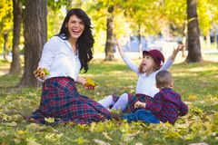 Mother plays with her children in the park in autumn stock photos