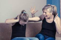 Beautiful young mother is scolding her daughter while sitting on sofa at home. Girl is covering her ears royalty free stock images