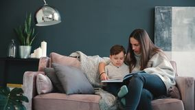 Beautiful young mother sitting on the sofa in your house the living room reads son a story in the ear and learn to read
