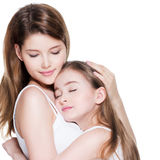 Beautiful young mother with a small daughter 8 years embrace each other royalty free stock images