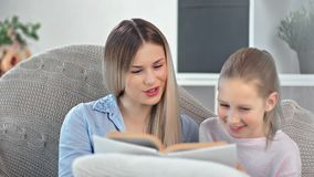 Beautiful young mother smiling reading book to cute teen daughter sitting on couch at home. Medium close-up. Happy laughing woman and girl kid looking at paper stock footage