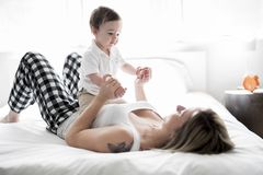 Beautiful young mother and son lying together on a bed Royalty Free Stock Photos
