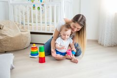 Beautiful young mother teaching her baby son playing with toys. Beautiful young mother teaching baby son playing with toys stock photos