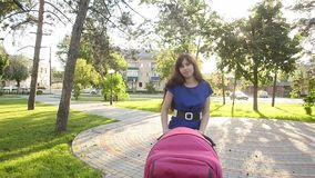 Beautiful young mother walking with baby stroller, family vacation on a day off in park in summer. Beautiful young mother walking with baby stroller, family stock footage