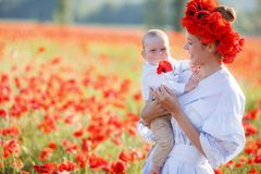 A happy mother with a small son in her arms on the endless field of red poppies on a sunny summer day Royalty Free Stock Photography