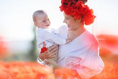 A happy mother with a small son in her arms on the endless field of red poppies on a sunny summer day Royalty Free Stock Image