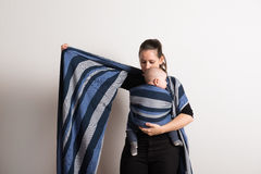 Beautiful young mother wrapping her son into sling. Studio shot. Royalty Free Stock Images