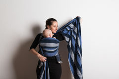 Beautiful young mother wrapping her son into sling. Studio shot. Royalty Free Stock Photo
