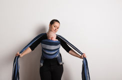 Beautiful young mother wrapping her son into sling. Studio shot. Stock Photography