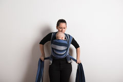 Beautiful young mother wrapping her son into sling. Studio shot. Royalty Free Stock Photos