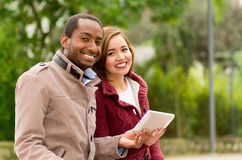 Beautiful young multi-ethnic couple having fun together at the park, holding his table while they smile at camera Stock Image