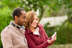 Beautiful young multi-ethnic couple having fun together at the park, holding his table and smiling in a blurred Stock Images