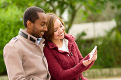 Beautiful young multi-ethnic couple having fun together at the park, holding his table and smiling in a blurred Royalty Free Stock Photography