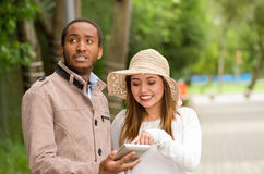 Beautiful young multi-ethnic couple having fun together at the park, man looking somewhere while woman watching his Royalty Free Stock Photos
