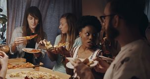 Beautiful young multiethnic women chat, smile eating pizza hanging out with friends at kitchen house party slow motion. stock footage