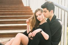 Beautiful young multiracial couple, student couple in love, sit wooden staircase in the city. Beautiful Turkish brunette guy hug a. Caucasian girl in black royalty free stock photos